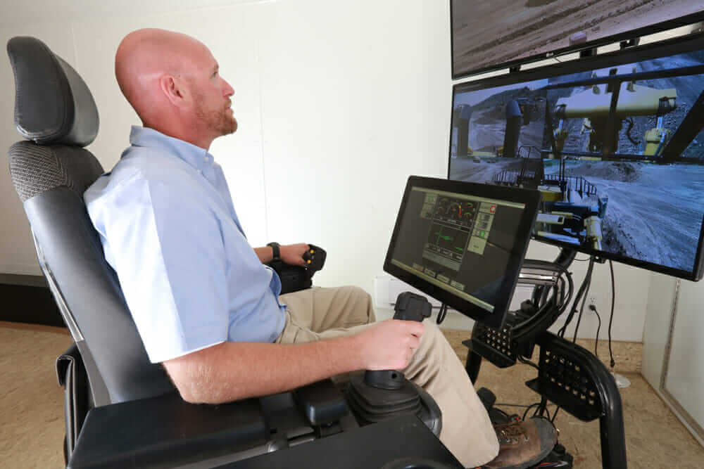 Human operator remotely supervising activities of autonomous construction vehicles
