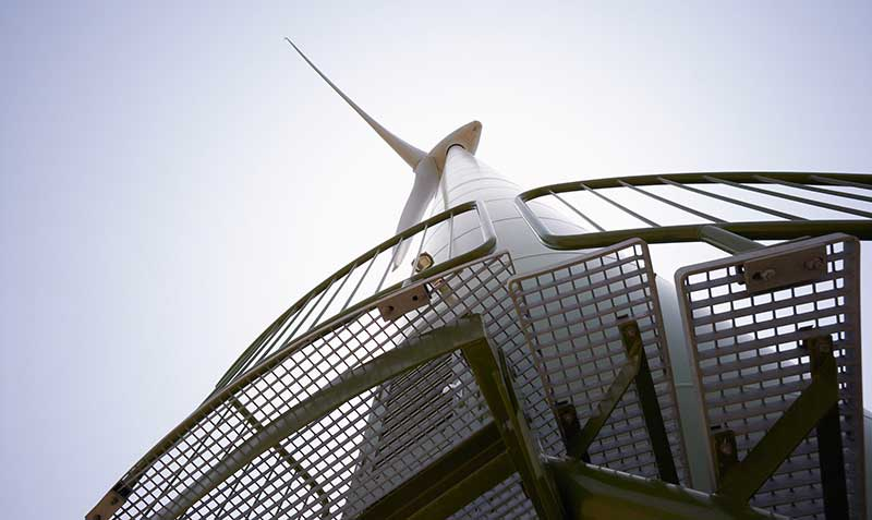Looking up at a wind turbine