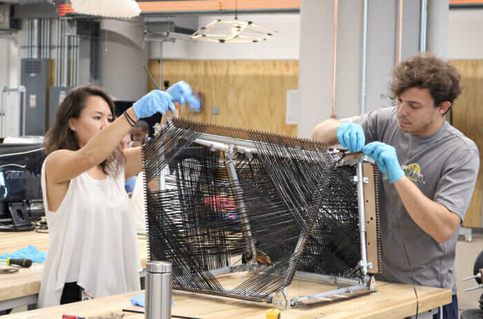 Project team hand weaving new carbon fiber architecture