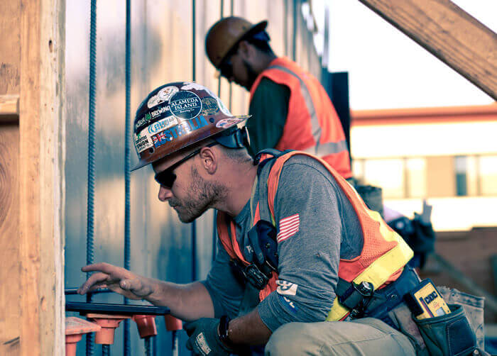Construction worker checking a tablet for project information.