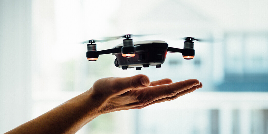 An aerial drone hovering above the operator's hand