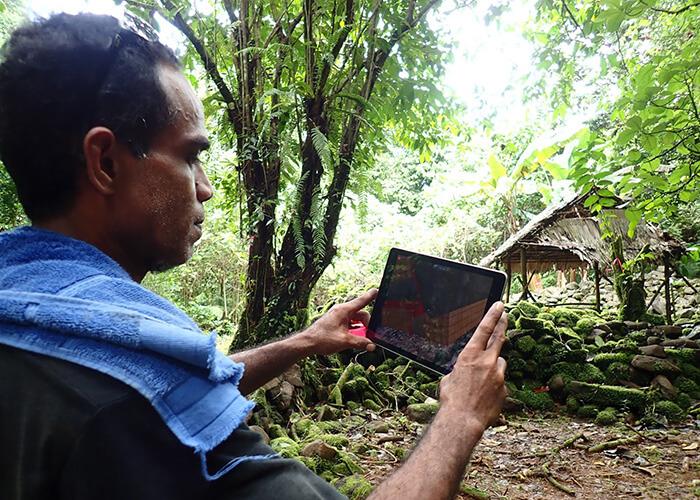 Salik Waguk, a Kosrean landowner responsible for clearing vegetation around the Menke Ruins, explores an AR presentation that overlays a historic depiction of a structure.