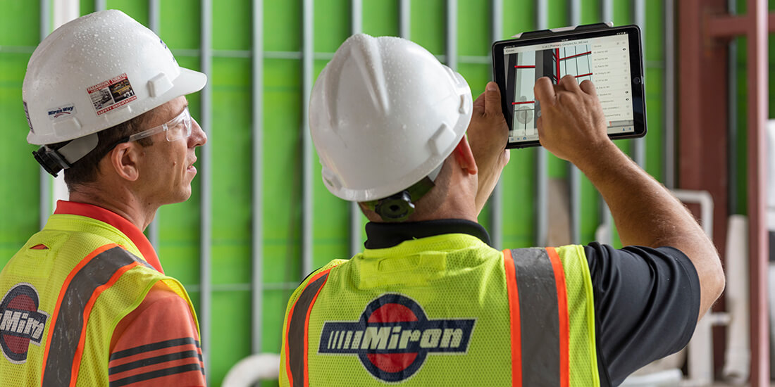 Two Miron Contruction workers review College of Pharmacy site plans on a tablet device.