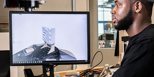 man viewing design software on a desktop monitor