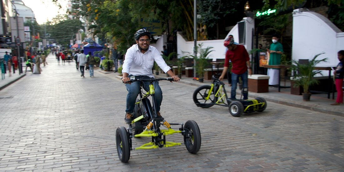 "A man rides Greendzine's Irrway NXP 500 ""electric trike"" in the street."