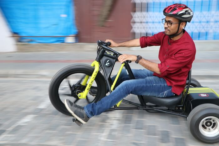 A man in a red shirt and helmet rides a go-kart-style three-wheeled electric vehicle