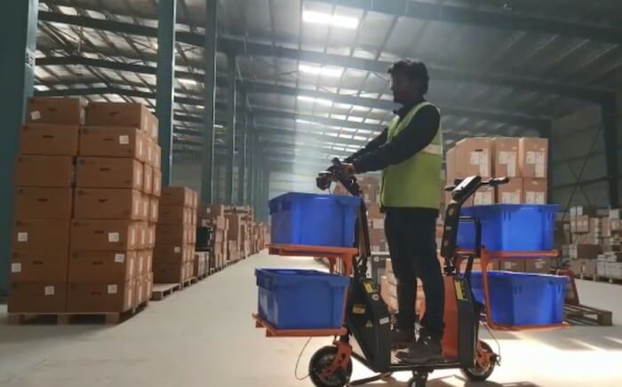 A man in a yellow safety vest rides a MOPTtro electric vehicle in a warehouse