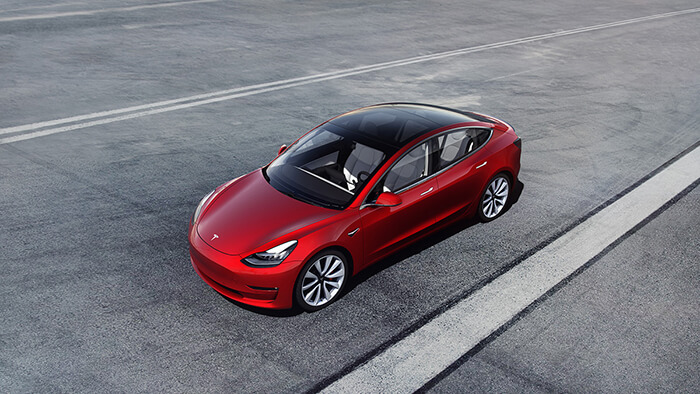Red Tesla Model 3 in a parking lot