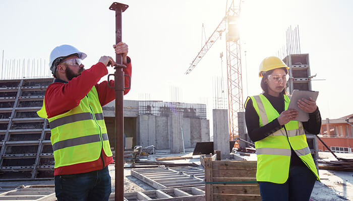 A construction worker is prepared to access data using a tablet onsite, thanks to preconstruction.