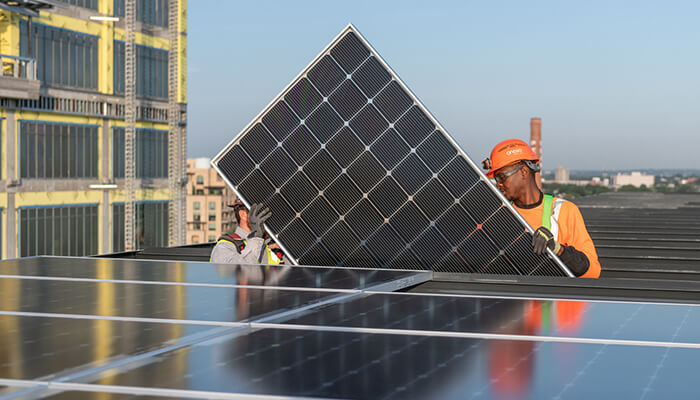 Two men carry a solar panel to a low-carbon development.