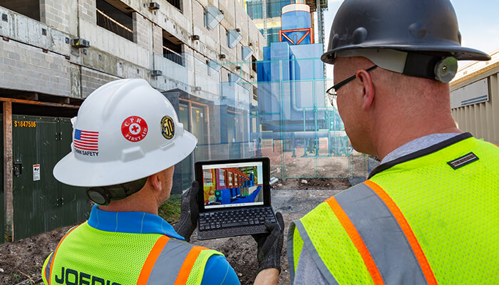 Two construction workers view a digital model on the jobsite, representing the implementation of global BIM mandates.