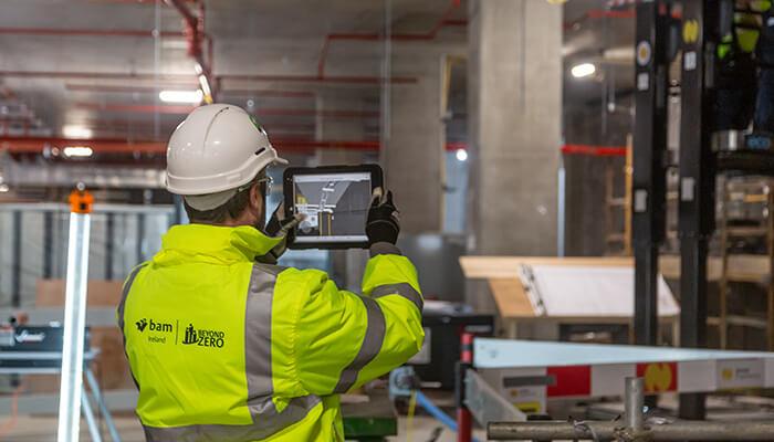 Construction workers view a digital model on a tablet, illustrating benefits of adopting global BIM mandates.