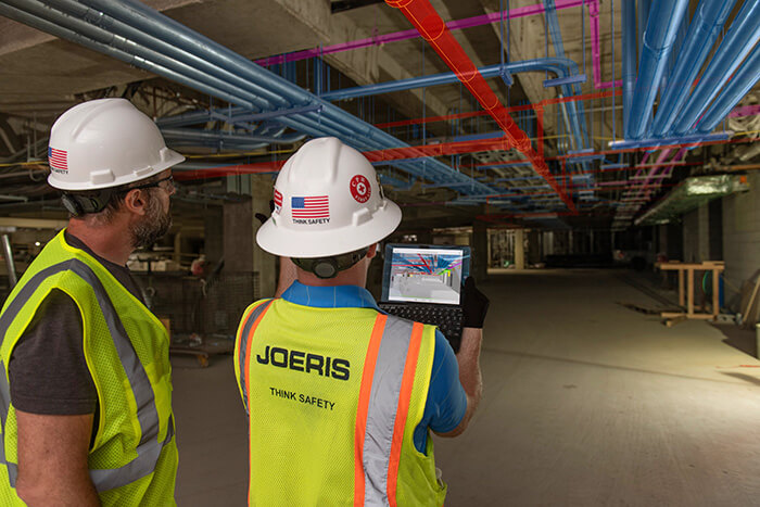 two construction workers viewing digital model on jobsite