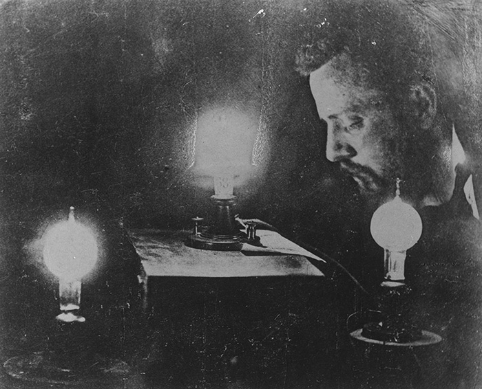 Grainy black and white photo of Charles Batchelor in profile with light bulbs
