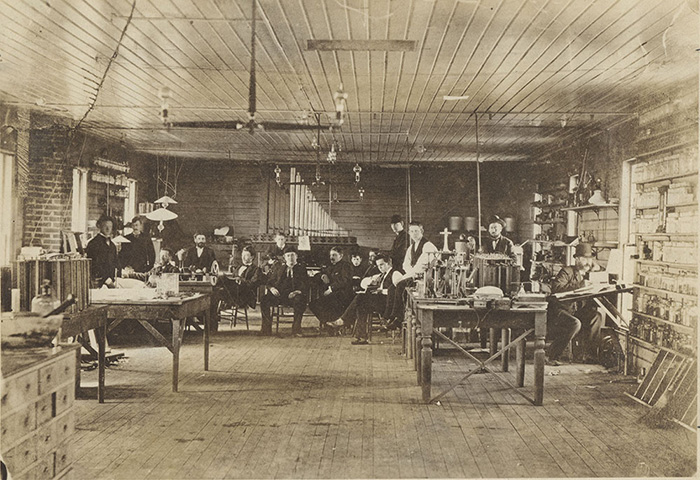 Sepia-toned photo of Thomas Edison seated with several of his Menlo Park lab staff