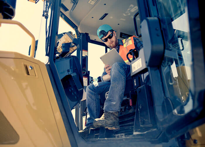 Construction vehicle operator looking at tablet