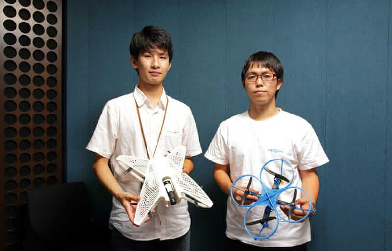 Yuki Ogasawara (links) und Ryo Kumeda (rechts) vom Team ROK konnten sich mit der blauen Drohne auf der rechten Seite den ersten Platz beim japanischen National Student Indoor Flying Robot Contest sichern. Mit freundlicher Genehmigung von Team ROK.
