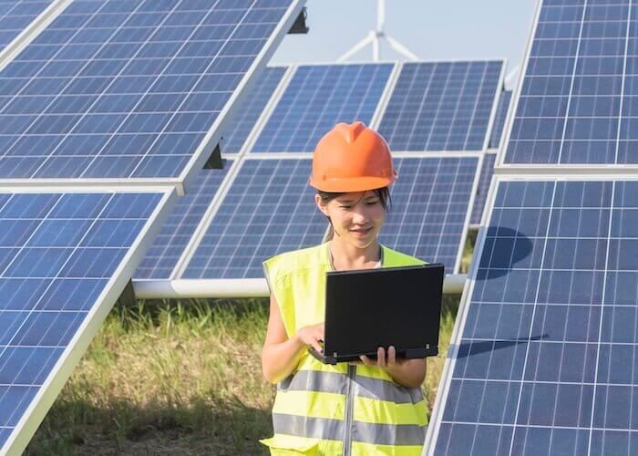 A woman in a hardhat with a laptop stands before an array of solar panels.