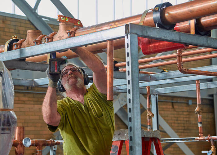 Ein Bauhandwerker der in Boston ansässigen TGA-Fachfirma Cannistraro arbeitet fernab der Baustelle an einer vorgefertigten Rohrleitungsbaugruppe.