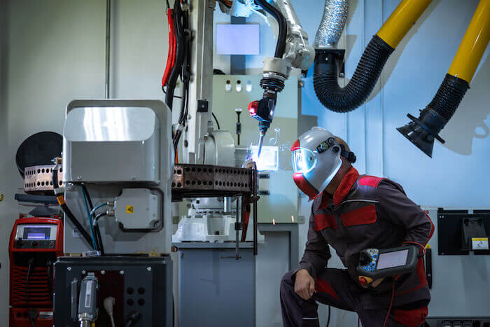 Industrie 4.0 – die Produktion der Zukunft: Ein Mann überwacht einen Schweißroboter in einem thailändischen Werk.