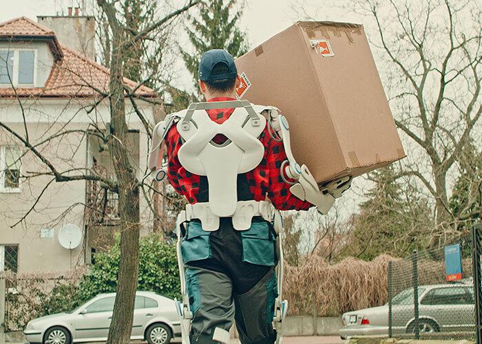 Wie verändert sich Arbeit durch KI und Automatisierung: Hier dient ein Exoskelett dem Boten als Kraftstütze beim Paketaustragen.