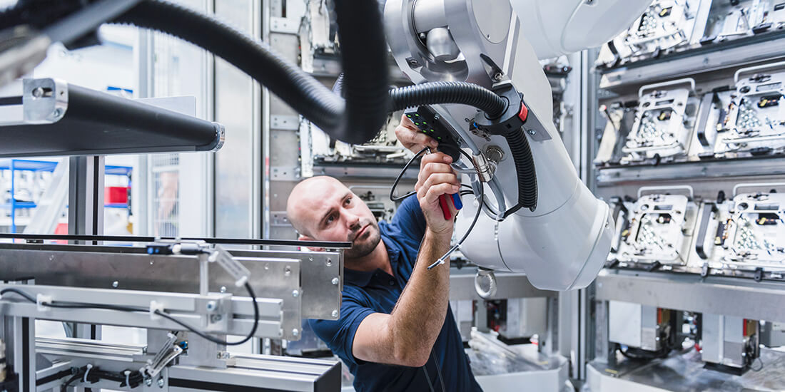 Mensch und Maschine Hand in Hand – früher hat der Mensch Teile manuell zusammengeschraubt, das erledigt heute der Roboter. Und der Mensch? Kümmert sich um das Laufen der Maschine.