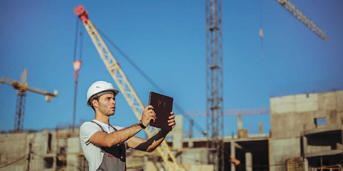 建設現場でタブレットを使用する若い労働者