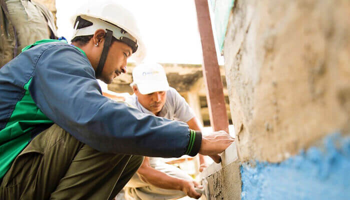 Volunteers for nonprofit Build Change work on retrofitting a building in Colombia.