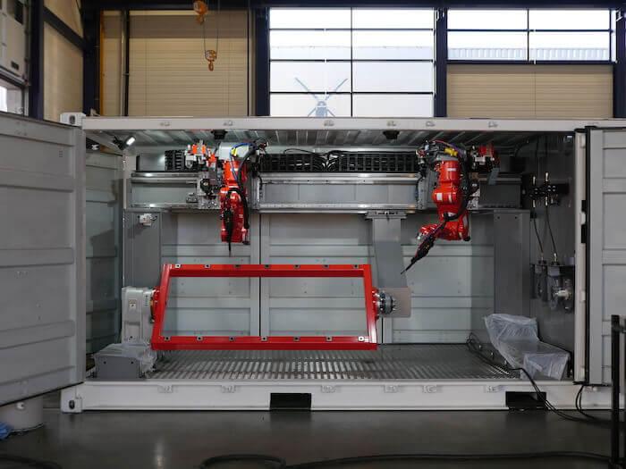 Voici un exemple de « boîte à outils » pour la fabrication additive : des robots à l'intérieur d'un conteneur de transport, prêts à travailler sur un chantier de construction.