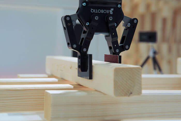CRoW's robotic arm positions a piece exactly, constantly evaluating the physical structure against the 3D model, and the user simply fastens it with a nail gun.