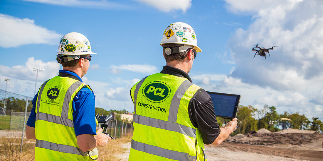 Two workers in hard hats operate a drone by tablet.