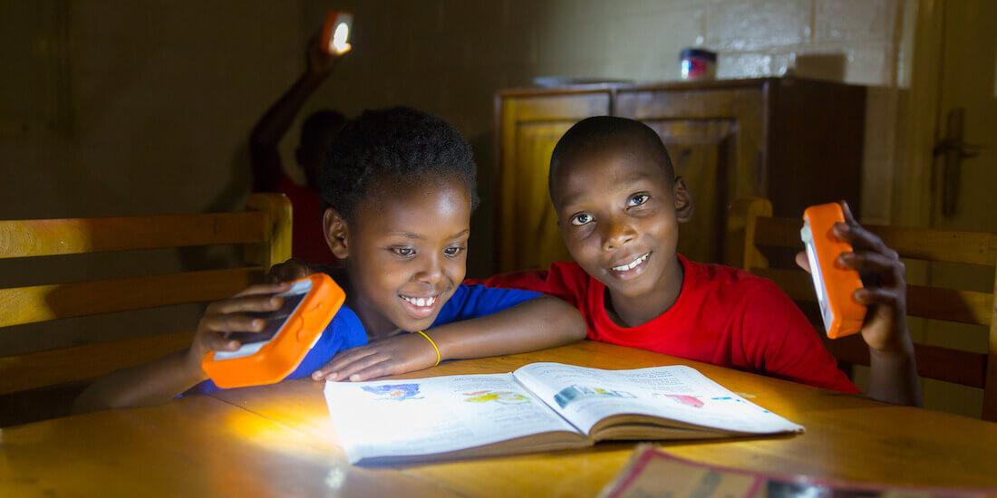 Povertà Energetica: Due ragazzi che studiano alla luce delle lampade SolarBuddy in Ghana.