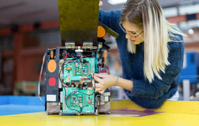 Employee on manufacturing floor working on circuit board of artificial-intelligence-enabled device