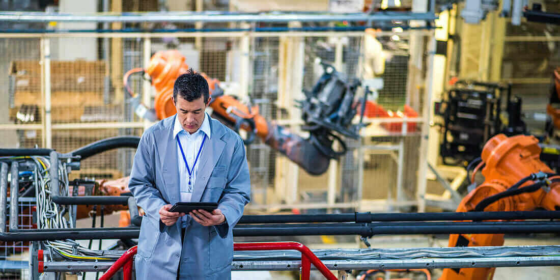 Manager reviewing notes at manufacturing facility using artificial intelligence and autonomous robots